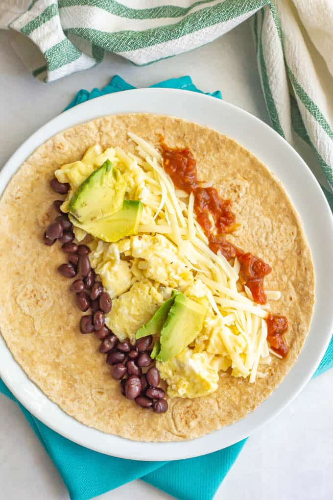 Black beans, eggs, cheese and salsa lined up on a tortilla with avocado slices on top