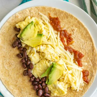 Tortilla with scrambled eggs, beans, cheese, salsa and avocado on a white plate