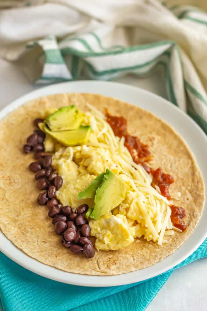 Breakfast burrito fillings laid onto a tortilla on a white plate