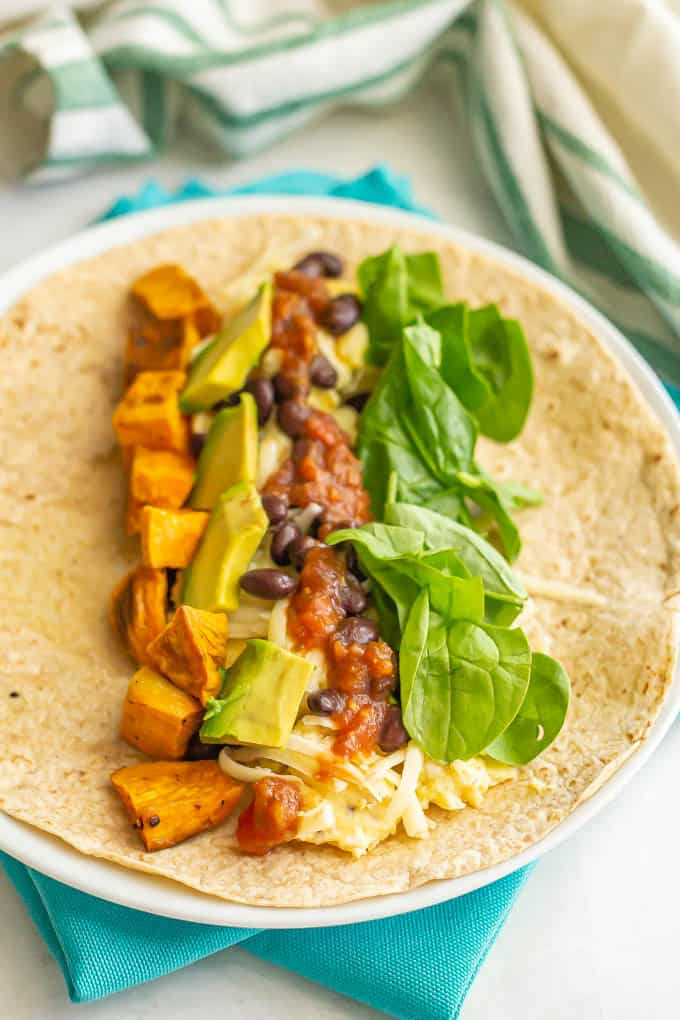 Scrambled eggs with veggies, beans, cheese and salsa in a whole wheat tortilla