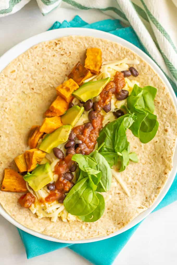 Veggie loaded breakfast burrito on a tortilla on a white plate