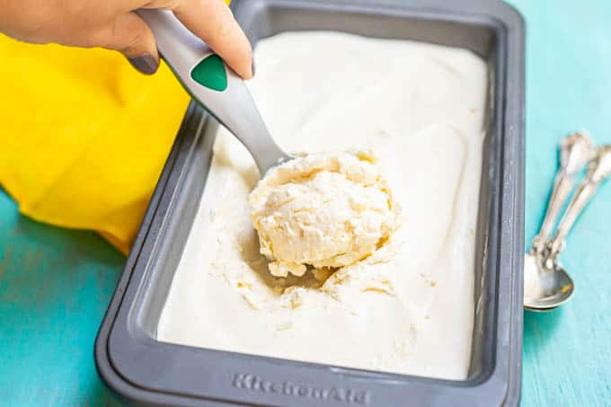 A hand scooping up a scoop of homemade vanilla ice cream from a bread pan