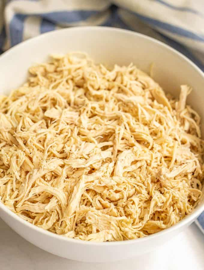 A large white bowl full of shredded chicken