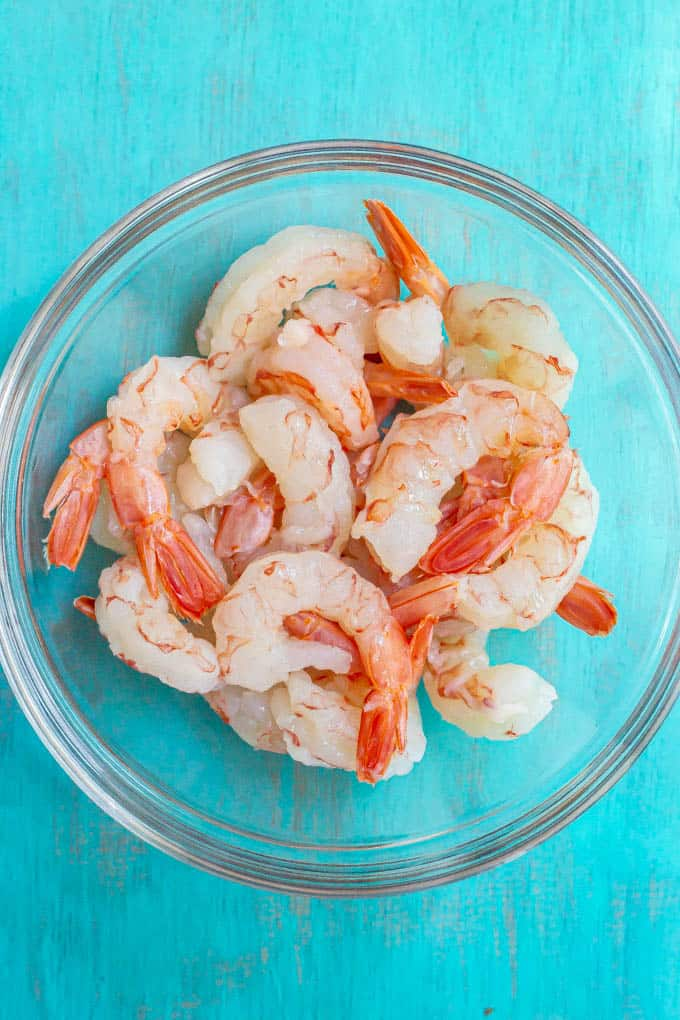 Peeled, deveined extra large raw shrimp in a glass bowl