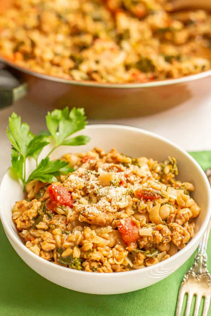 White bowl filled with a turkey sausage and farro mixture with veggies served on green napkins with a fork