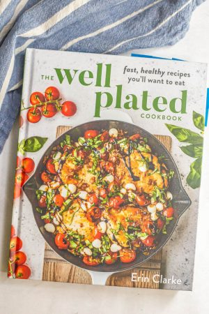 Cover of the Well Plated Cookbook on a counter with a blue striped towel nearby