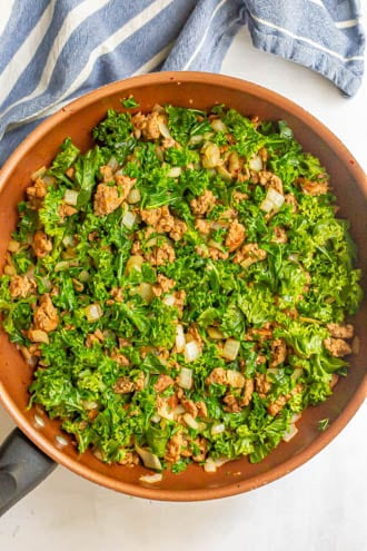 A skillet of turkey sausage and onions and kale being wilted in