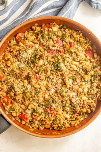 A turkey sausage skillet with farro, kale and white beans