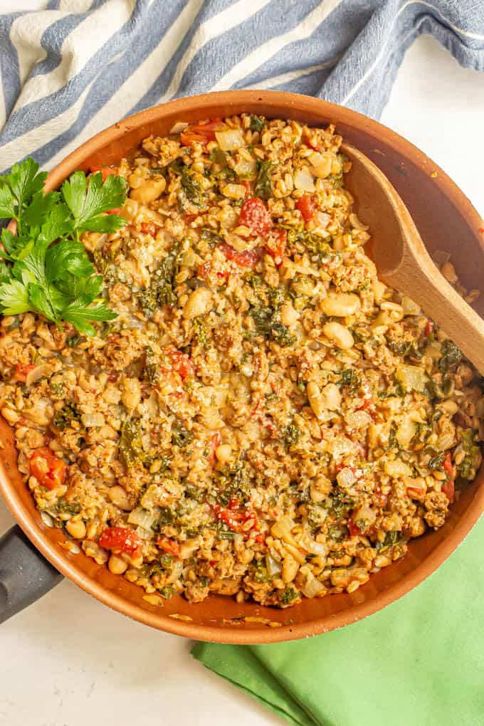 Large skillet with turkey sausage, farro, white beans, kale and tomatoes with a sprig of parsley