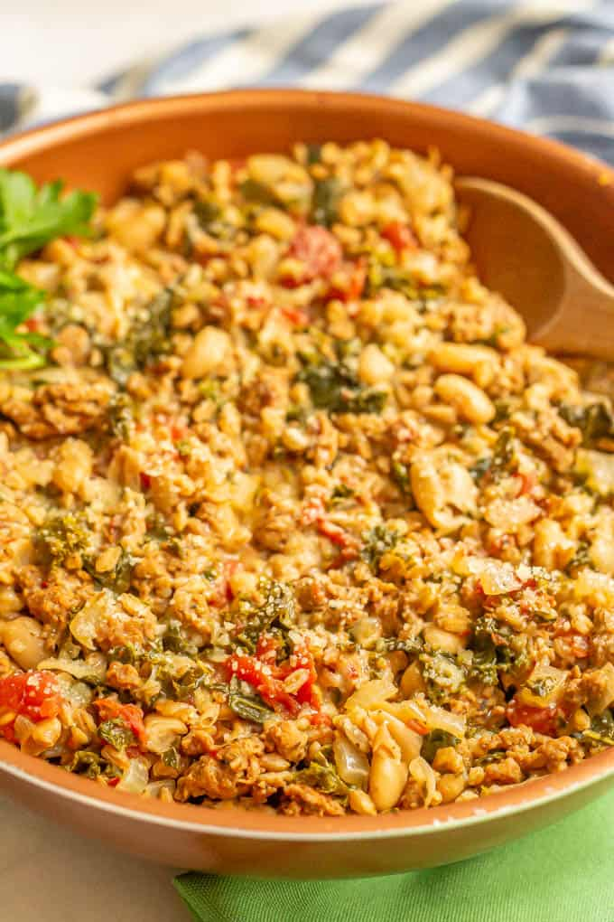 A hearty skillet with turkey sausage, greens, beans and farro with Parmesan sprinkled on top