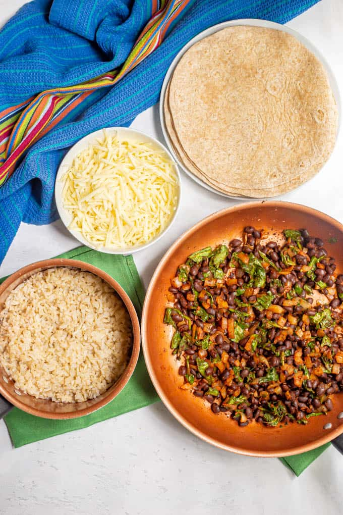 Ingredients laid out in separate pans and dishes for making vegetarian bean burritos
