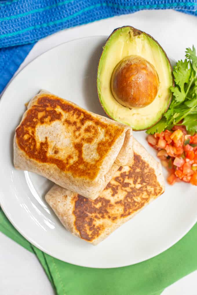Seared wrapped burritos on a white plate with avocado, salsa and cilantro for toppings