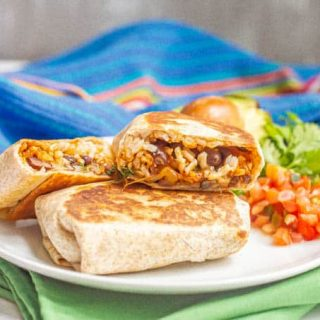 Halved bean and rice burrito stacked on a plate with colorful napkins nearby
