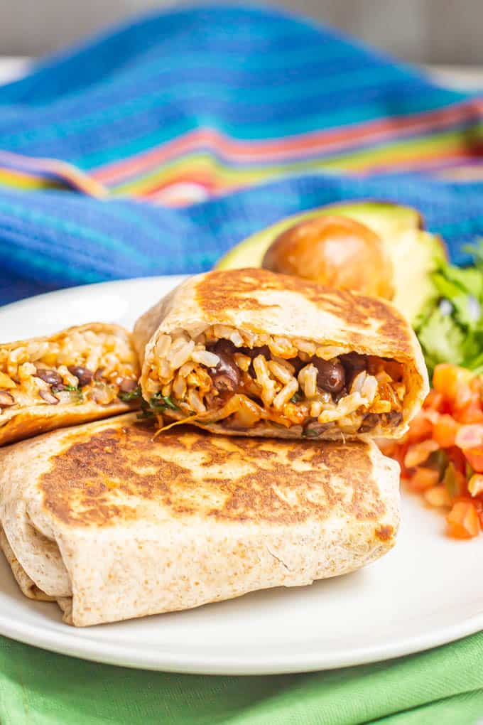 Stacked vegetarian burritos on a white dinner plate with toppings nearby