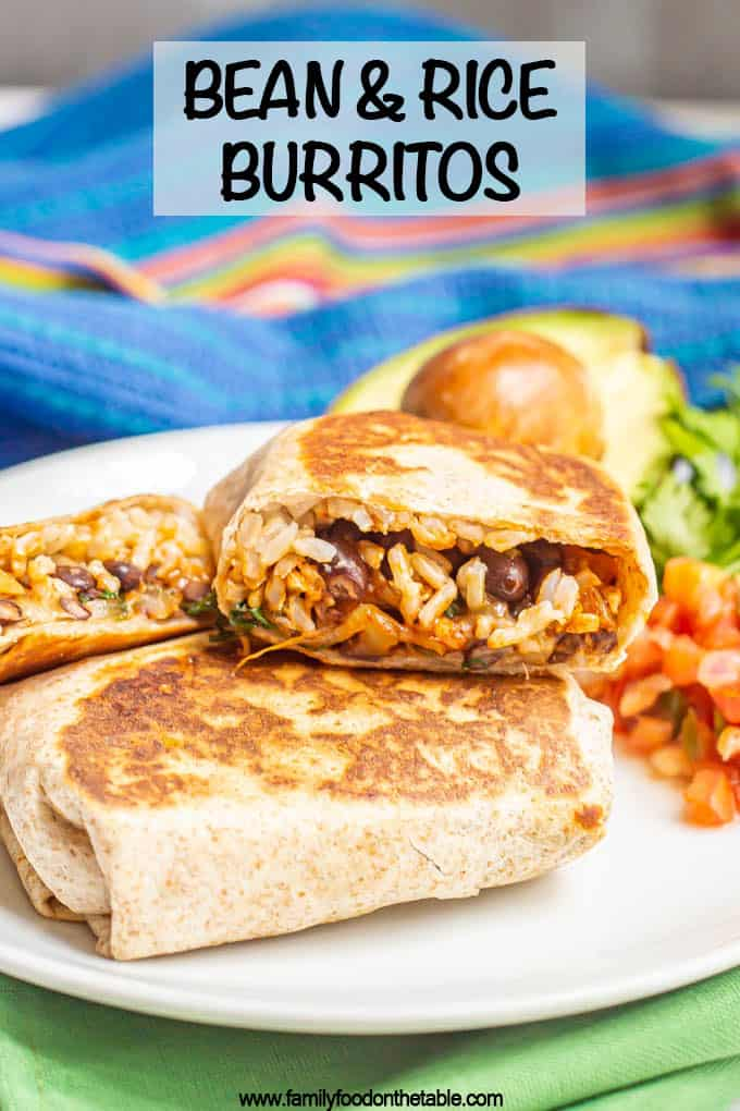 A cut bean and rice burrito stacked on top of another on a white serving plate with toppings nearby and a text overlay on the photo