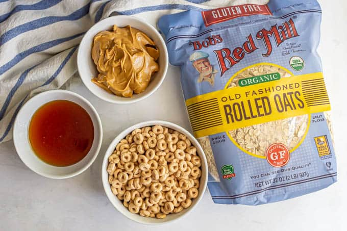 Bob's Red Mill oats alongside bowls of peanut butter, honey and cereal laid out on a counter