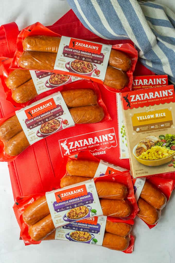 A collection of Zatarain's smoked sausages and Zatarain's yellow rice boxes spread out
