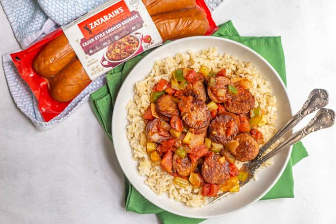 Cajun sausage and veggie mixture served over white rice with a package of Zatarain's sausages nearby