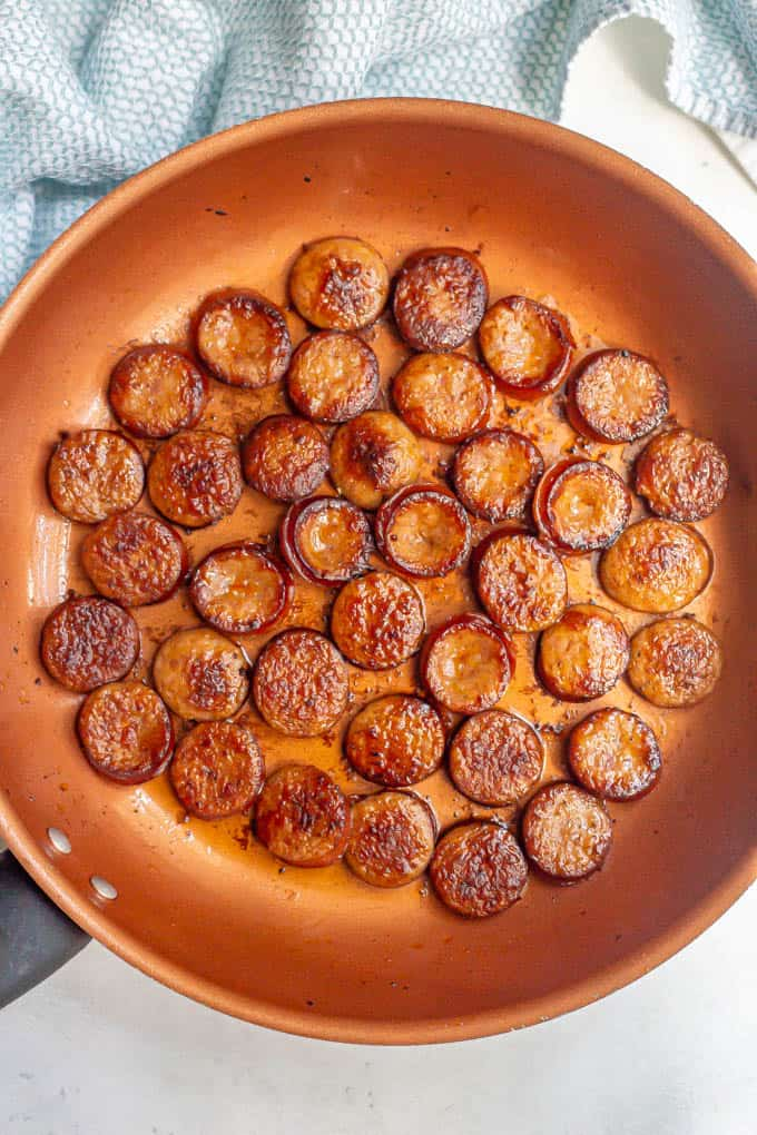 Sliced, browned smoked sausage rounds in a large pan