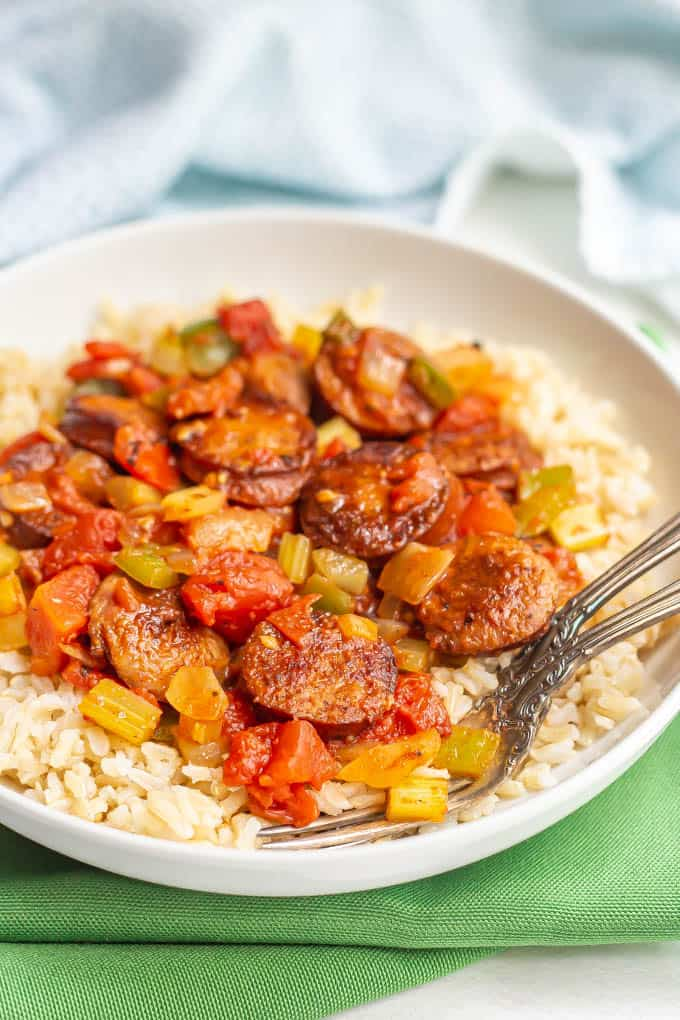 Cajun sausages and veggies served over rice in a large white bowl with forks alongside