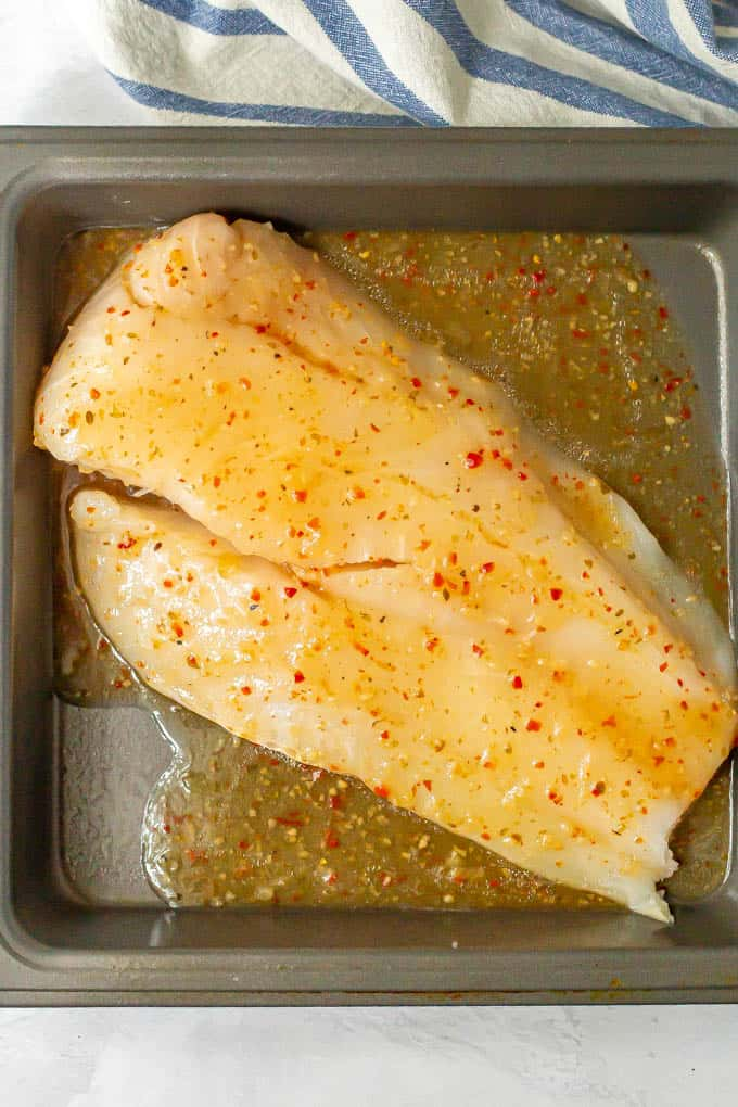 A piece of raw cod in a baking dish covered in Italian dressing before being cooked