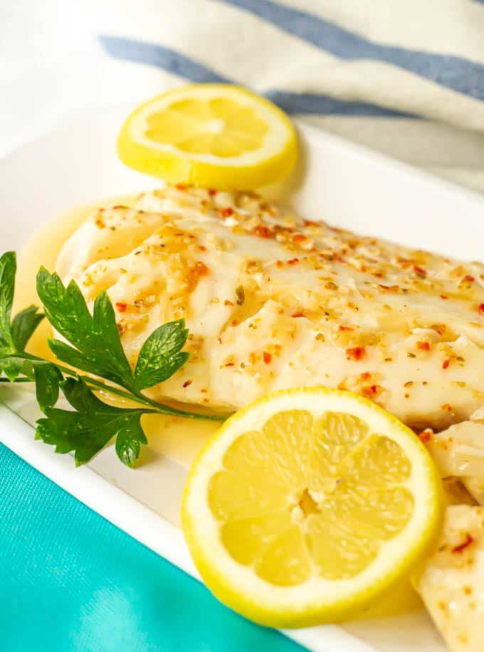 Baked cod with Italian dressing served on a white platter with lemon slices and parsley as garnishes