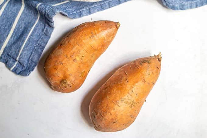 Two scrubbed sweet potatoes on a counter with a blue striped towel nearby