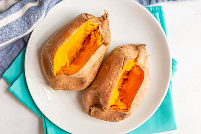 Two sweet potatoes on a white plate cut open after being cooked