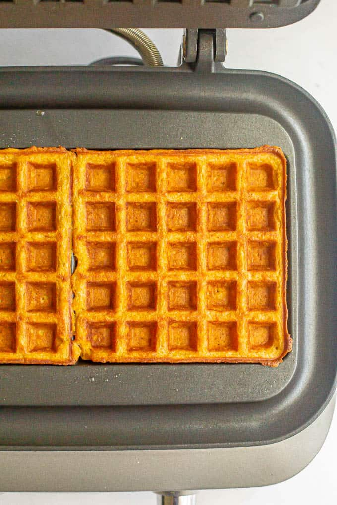 Big square pumpkin waffles in a waffle iron after cooking