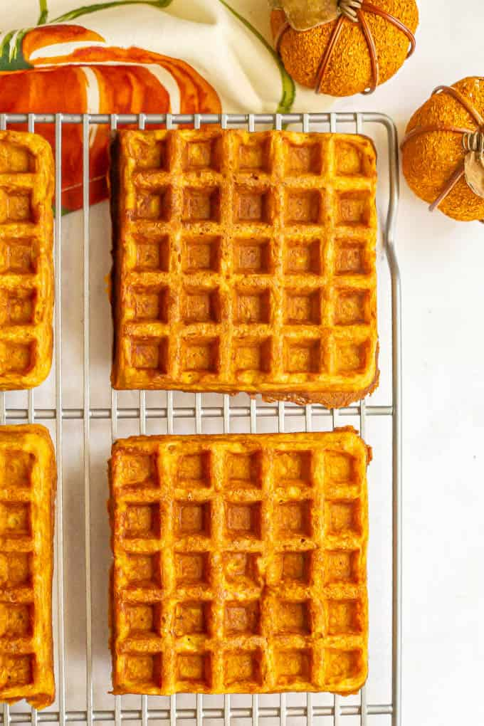Close up of homemade pumpkin waffles on a cooling rack with pumpkin decor nearby