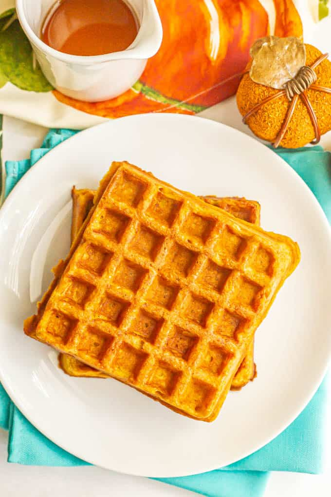 Healthy pumpkin waffles served on a white plate with maple syrup in a serving dish nearby