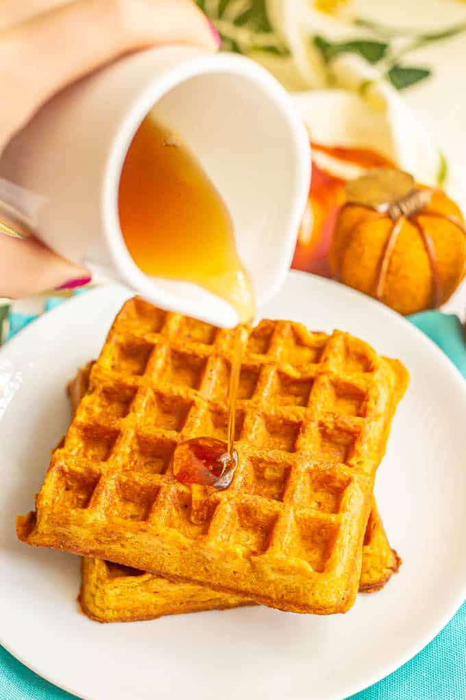 Maple syrup being poured over two pumpkin waffles stacked on each other on a white plate