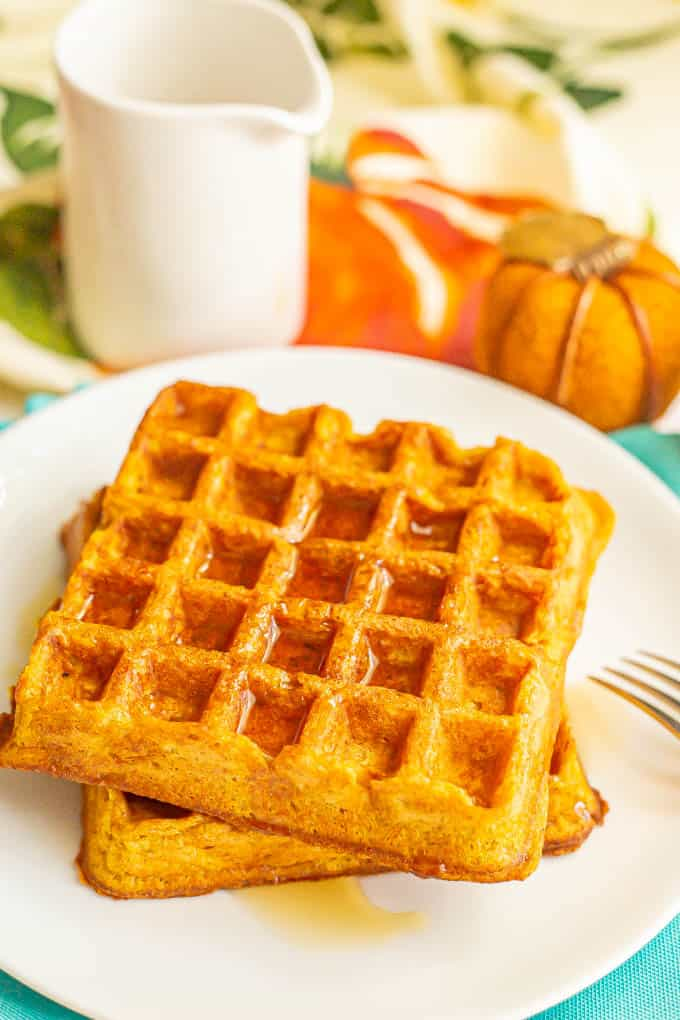 Two large pumpkin waffles on a plate with maple syrup on top and a fork to the side