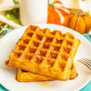 Two large pumpkin waffles stacked on a white plate with maple syrup on top and a fork to the side