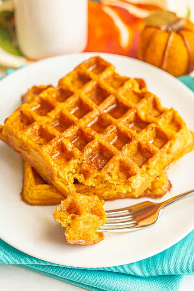 A fork taking a bite of a stack of pumpkin waffles with maple syrup on top