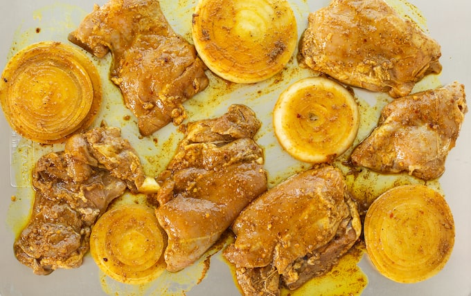 Marinated chicken thighs and onion slices laid out on a baking sheet