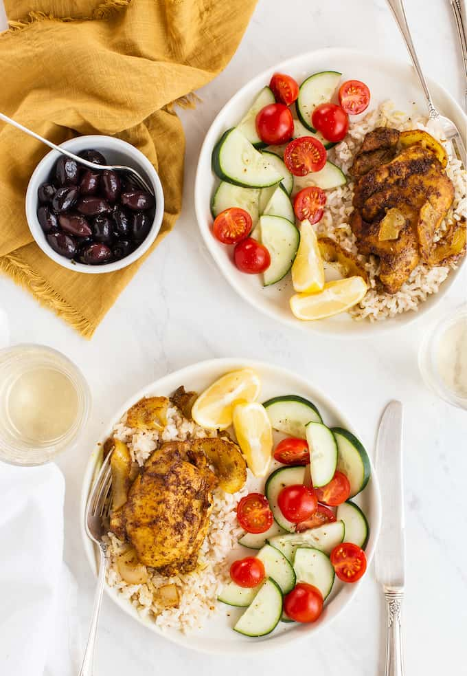 Two bowls of rice with chicken shawarma and a cucumber and tomato salad