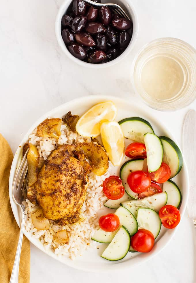 A dinner plate of baked chicken shawarma over rice with a cucumber tomato salad