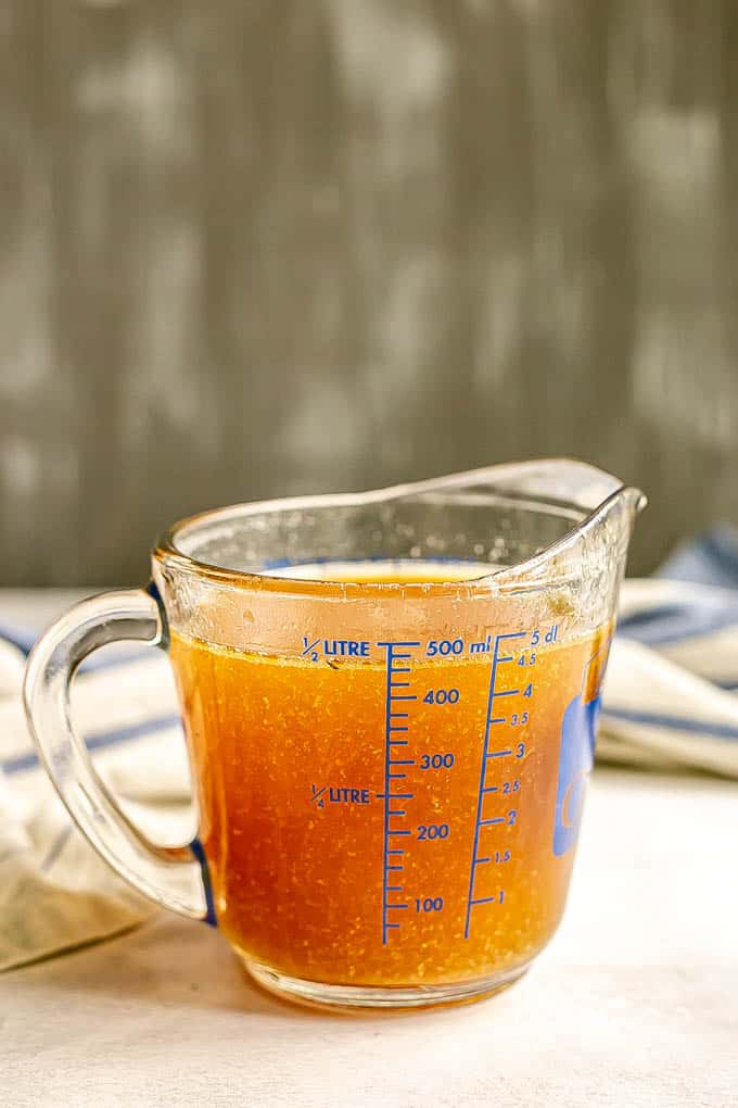 A glass measuring cup full of turkey drippings that have been strained and skimmed of fat