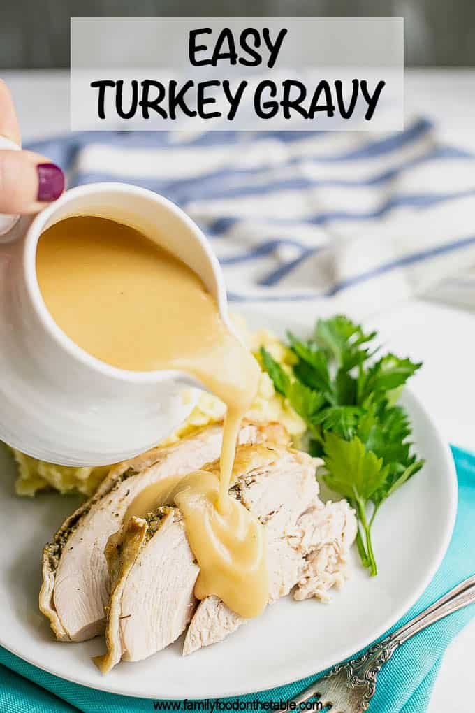 Gravy being poured over sliced turkey on a white dinner plate