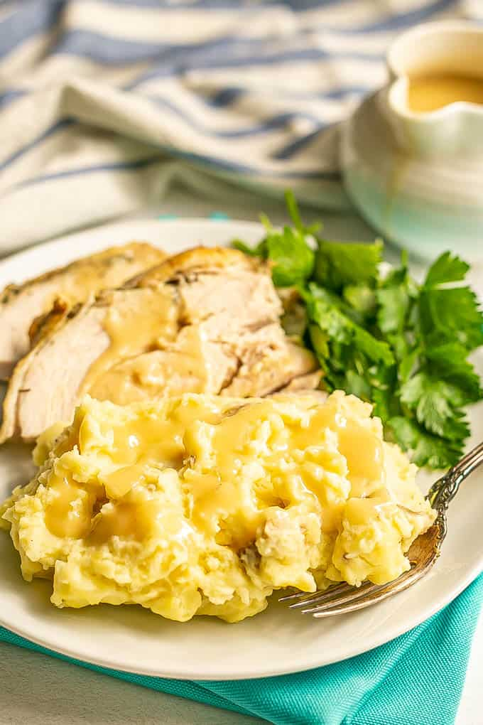 Mashed potatoes topped with gravy on a white plate with sliced turkey and a fork alongside