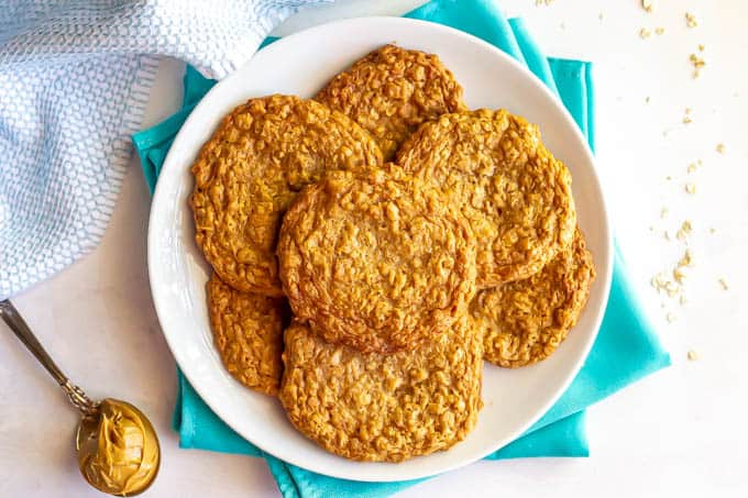 A white plate full of oatmeal peanut butter cookies with scattered oats and a spoonful of peanut butter nearby