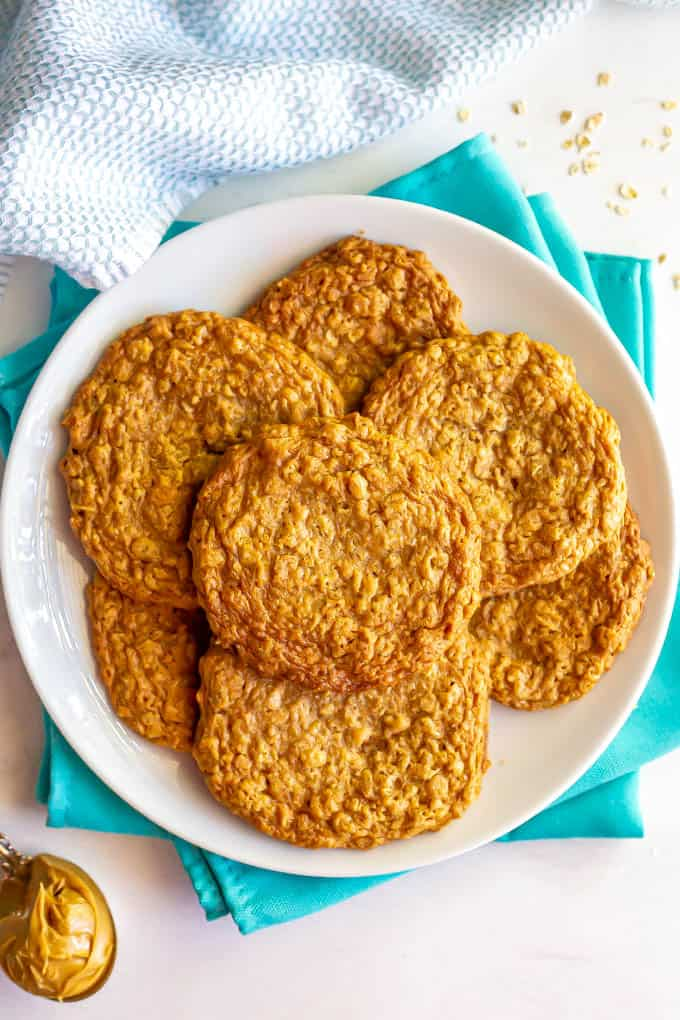 A plate full of old fashioned peanut butter oatmeal cookies and teal napkins underneath