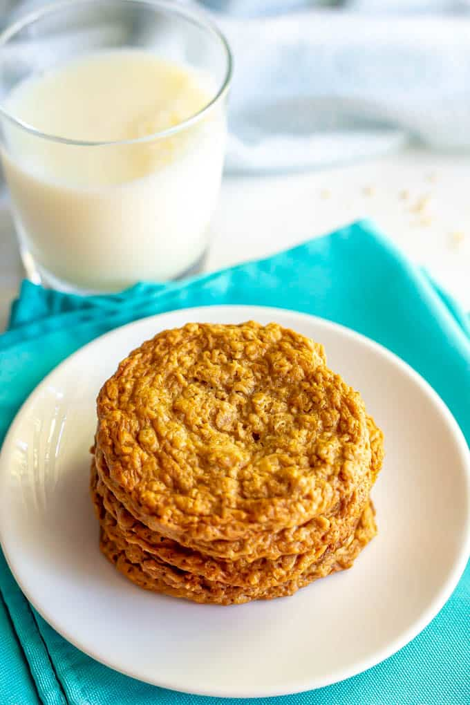 A stack of peanut butter cookies on a white plate with a glass of milk in the background