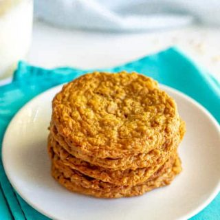 A stack of peanut butter oatmeal cookies on a white plate with a glass of milk in the background