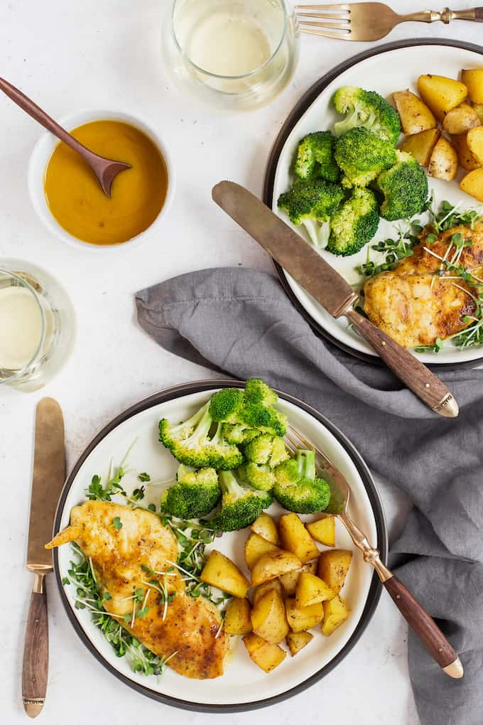 Two plates with honey mustard chicken, broccoli and roasted potatoes, plus utensils and wine glasses