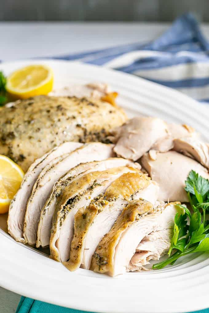 Perfectly cooked sliced turkey breast with herbs and skin served on a white platter
