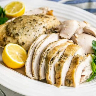 Crock pot turkey breast sliced and served on a white platter