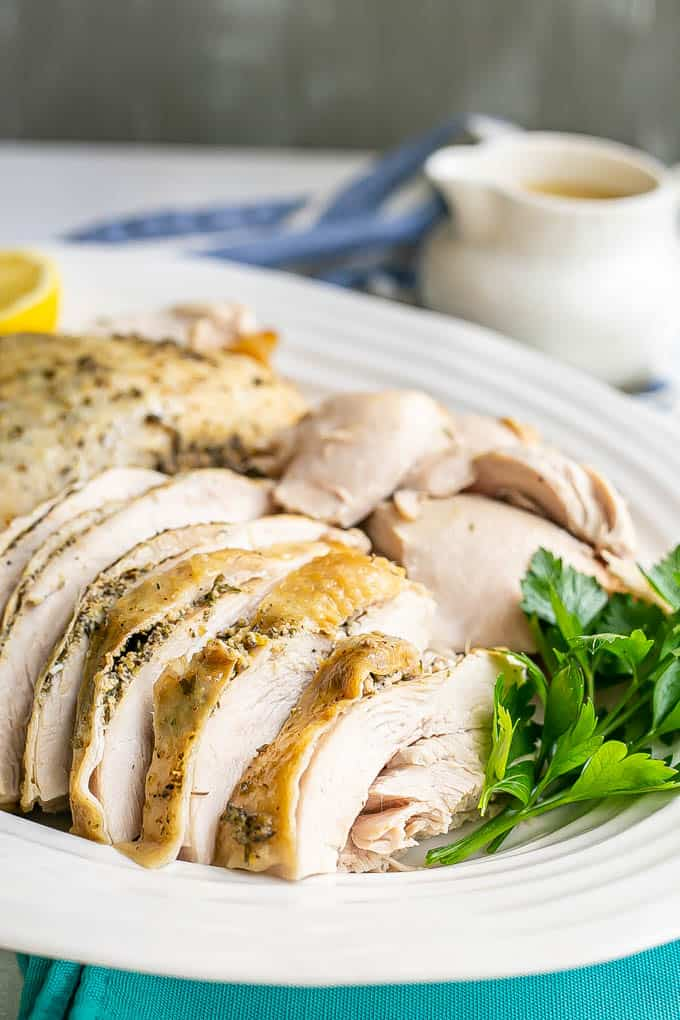 Close up of sliced skin on turkey breast served in a large white platter