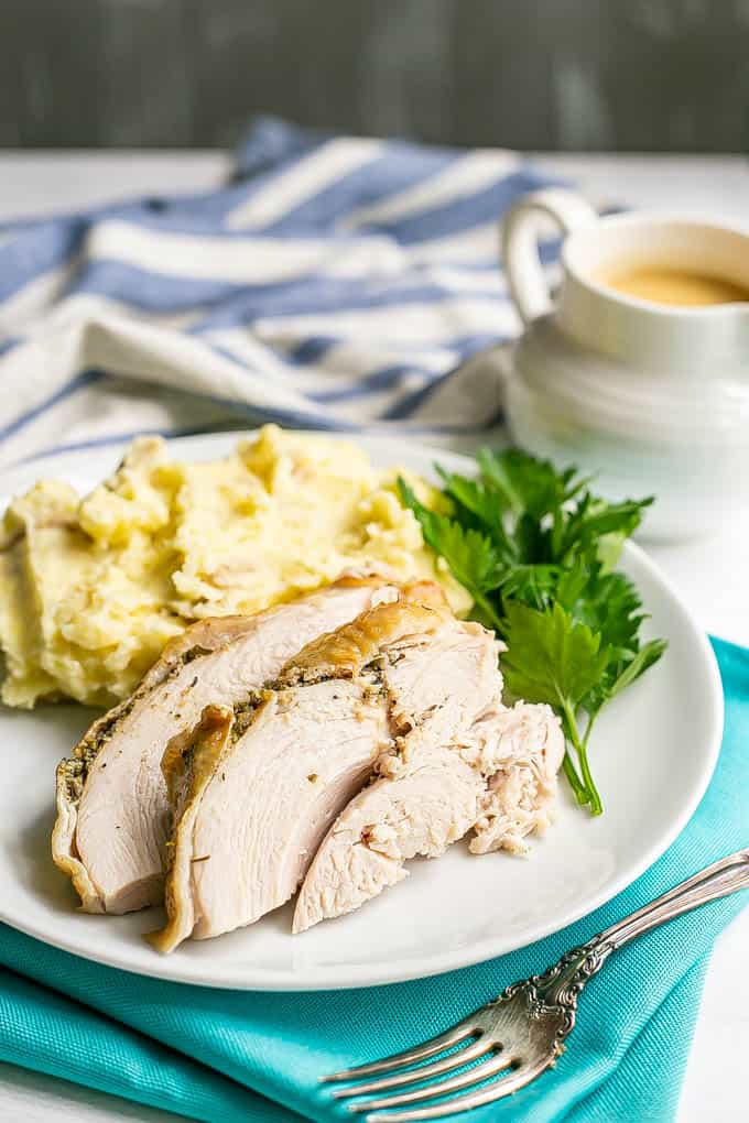 Sliced cooked turkey breast served on a white dinner plate with mashed potatoes and parsley